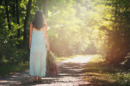 Beautiful woman walking forest path in soft light. Peace and harmony Standard-Bild