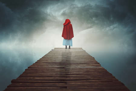 Red hooded figure lost in a surreal land .  Ethereal and fantasy
