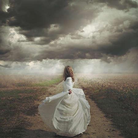 荒涼とした道路で踊る女性。劇的かつシュールな cloudscape 写真素材 - 51073062