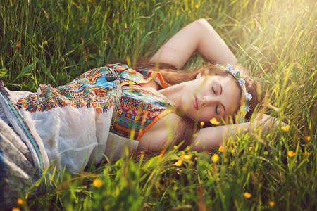 armonia: Mujer hermosa del hippie pacíficamente dormir en prado de primavera
