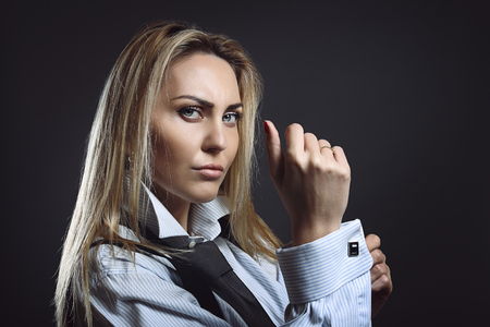 Businesswoman with tough expression wearing cufflink. Power and boldness