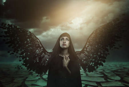 Dark angel with broken wings looks at paradise lost . Fantasy and myth