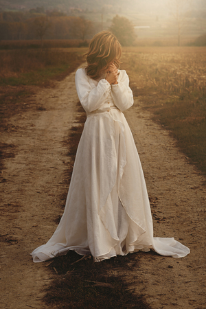 Lone woman with vintage bride dress in countryside . Purity and innocence