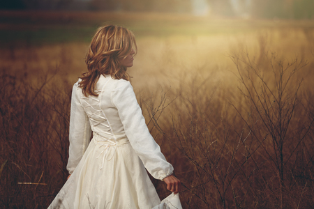 the innocence: Beautiful woman walking in a field. Purity and innocence Stock Photo