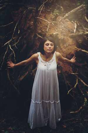 Free young woman in the forest. Ethereal and innocent