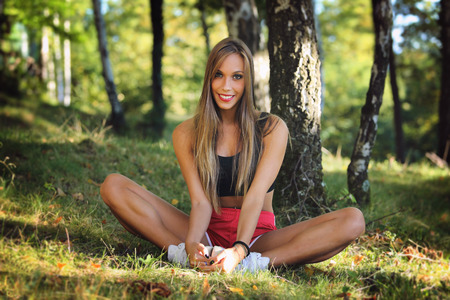 Smiling happy woman stretching on grass. Sport and outdoor