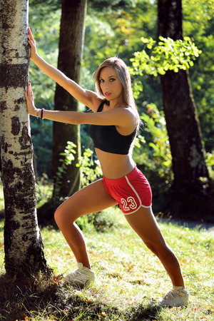 outdoor sport: Fitness model stretching against a tree .Sport and outdoor