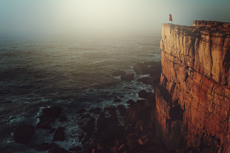 photomanipulation: Lonely person on sea cliff. Dark and surreal