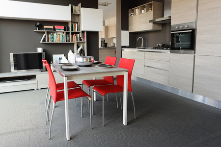 modern dining room: Full view of a modern kitchen and dining room . Cream and red