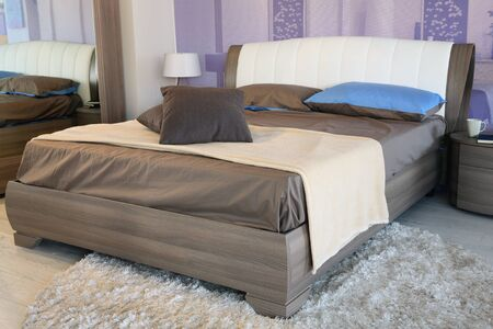 furniture store: Stylish cream and brown bed . Furniture store