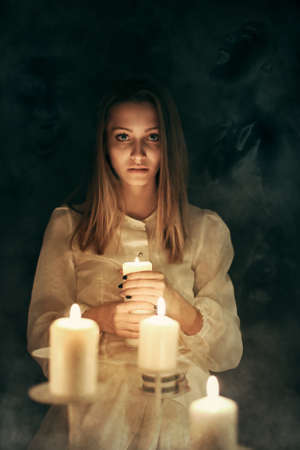 candle lights: Young woman with candle lights surrounded by ghosts . Halloween and scary