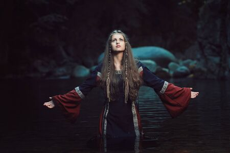 Medieval beautiful woman praying in a stream . Fantasy colors Stock Photo