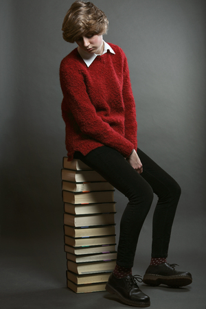 seated: Young student seated on a stack of books. Sad expression Stock Photo