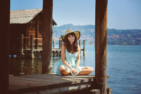summer dress: Beautiful young woman with summer dress . Wood cabin and lake