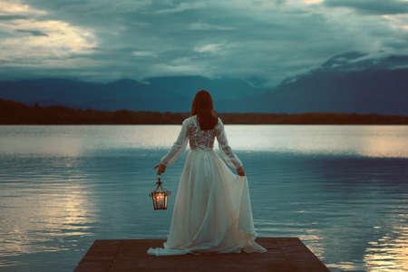 femme romantique: Femme en attente sur un quai de lac avec lanterne. Surréaliste et romantique
