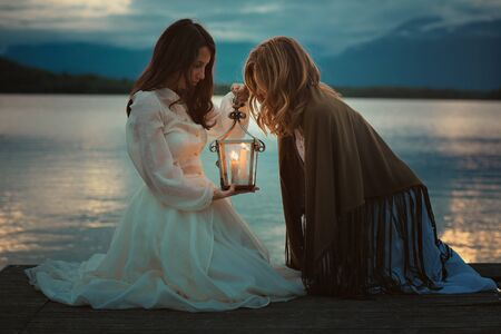 lost lake: Beautiful women looking into warm light lantern. Dramatic cloudscape
