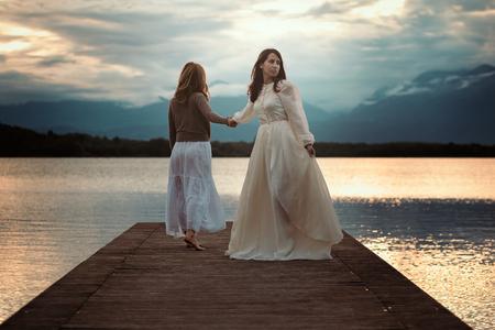 feelings and emotions: Beautiful women walking on lake pier. Surreal sunset