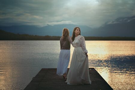lost lake: Two women on a lake pier . Surreal and ethereal Stock Photo