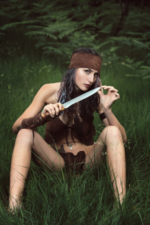 Beautiful wild huntress in the forest. Outdoor and ethnic