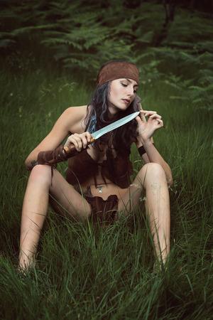 mujer pirata: cazadora nativa esperando a su presa en el bosque Foto de archivo
