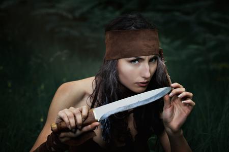 gaze: American indian hunter playing with a knife . Dangerous gaze