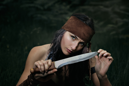 pagan: Dangerous gaze from indian hunter . Portrait with knife Stock Photo