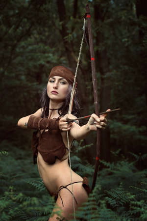 Beautiful huntress aiming with bow . Forest survival