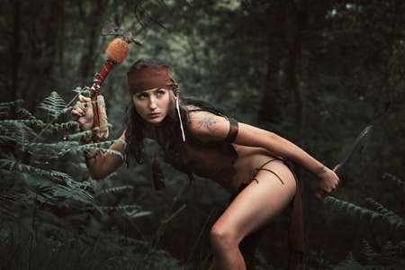 squaw: Indian female warrior hunting in the forest . Tomahawk weapon