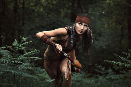 cherokee: Beautiful indian huntress in a green forest . Native warrior