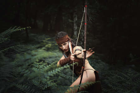 Deadly female hunter aiming with bow. Outdoor portrait Stock Photo