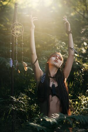 enlightment: Beautiful native shaman praying in the forest. Free spirit
