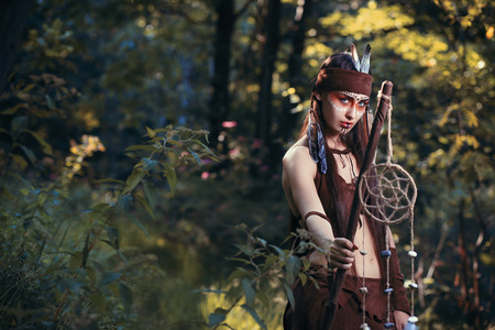 enlightment: Beautiful female shaman posing with dream catcher in a forest. Native spirituality