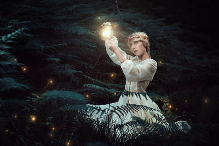 Fairy young woman hunting fireflies in the woods . Fantasy and magic Stock Photo