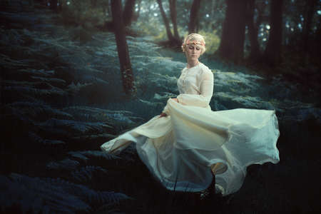 white woman: Ethereal woman dancing in dreamy forest. Fantasy and surreal Stock Photo