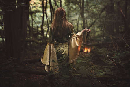 Mysterious woman walking in fairy forest with a lantern. Fantasy