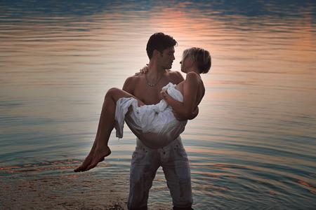 parejas jovenes: Pareja romántica en aguas del lago al atardecer. El amor y la ternura