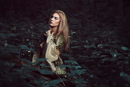 Young woman in a dark fairy forest. Medieval dress