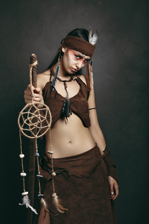 indigenous medicine: Beautiful shaman with dream catcher rod. Studio shot Stock Photo
