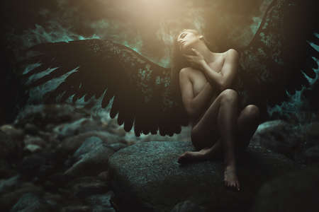Fallen angel with black wings . Dark fantasy manipulation Stock Photo