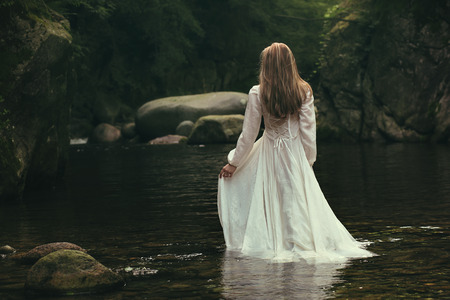 Romantic woman walks into a green stream. Ethereal and dreamy