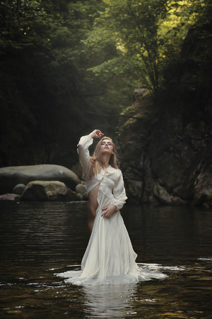 Beautiful woman posing in dreamy mountain stream. Fantasy and surreal
