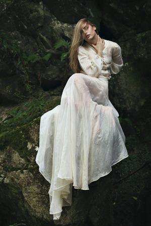 atmosfera: Mujer hermosa que presenta en las rocas y el musgo. atmósfera de ensueño Foto de archivo