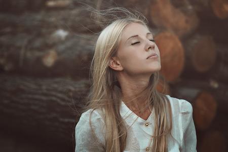 ojos cerrados: Hermosa mujer disfrutando de viento de otoño. Ojos cerrados