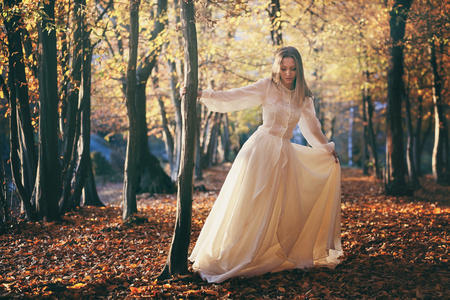 autumn colors: Woman with victorian dress dancing in autumn woods. Seasonal colors Stock Photo
