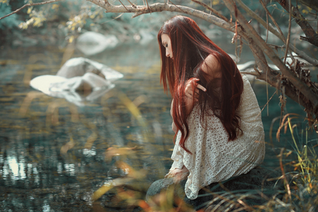 Thoughtful red hair woman looking at stream waters. Autumn colors