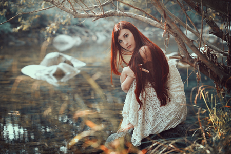 realm: Beautiful woman posing on a stream shore . Autumn colors