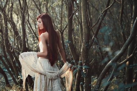 赤い髪の美しい女性が森の中でポーズします。空気のようなロマンチックです 写真素材