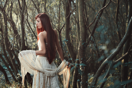 Beautiful red hair woman posing in the woods . Ethereal and romantic