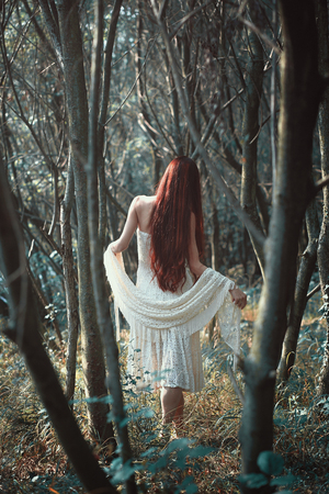 Woman with long red hair walks in weird forest . Ethereal and romantic