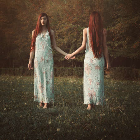 Red hair woman with her mirror soul. Surreal and conceptual Stock Photo